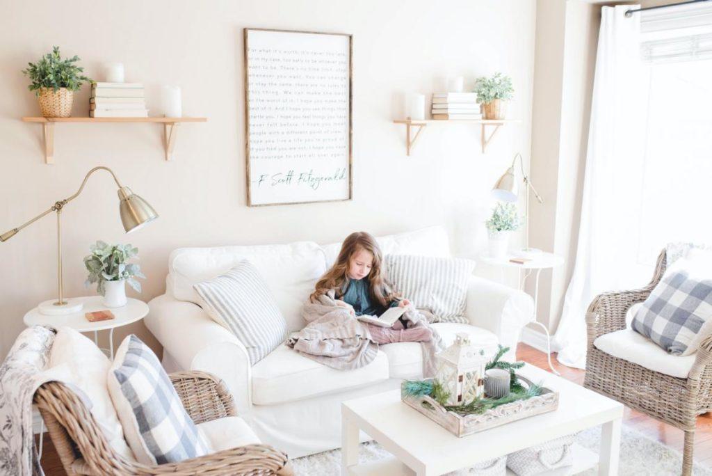 Ein helles Wohnzimmer mit natürlichen Akzenten und ein kleines Mädchen auf dem Sofa die ein Buch liest