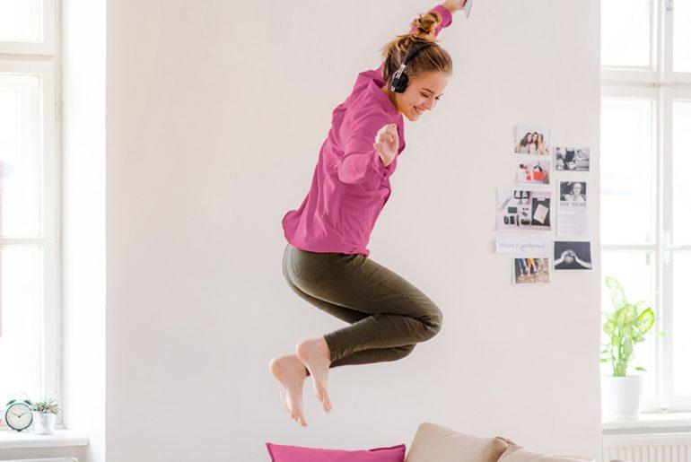 Eine Frau die auf dem Bett springt