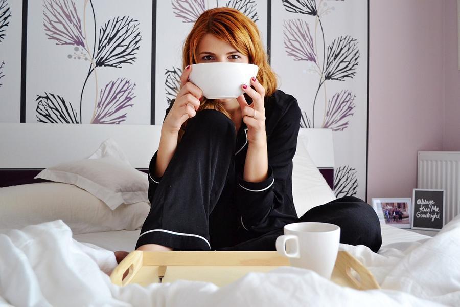 Junge Frau im Pijama auf dem Bett mit einer Tasse in der Hand